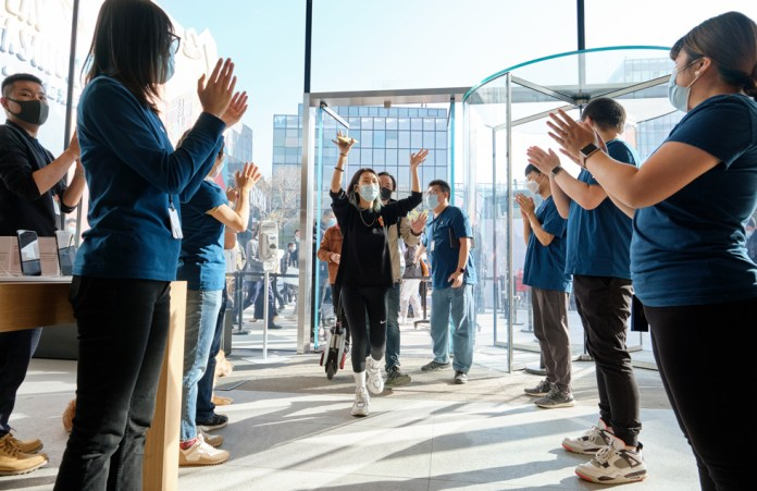 I dipendenti di Apple Sanlitun accolgono i clienti che arrivano in negozio per scoprire i nuovi iPhone 12 Pro Max e iPhone 12 mini.