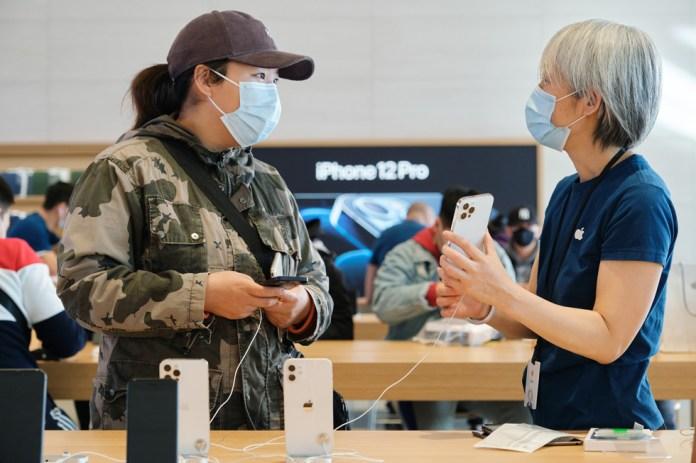 Una dipendente dell'Apple Sanlitun risponde alle domande di una cliente su iPhone 12 Pro Max.