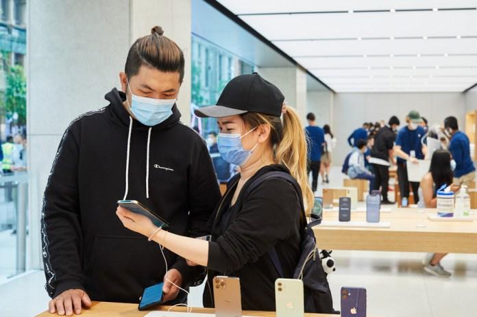 Due clienti di Apple Sydney provano il nuovo iPhone 12 Pro Max a un tavolo dei prodotti.