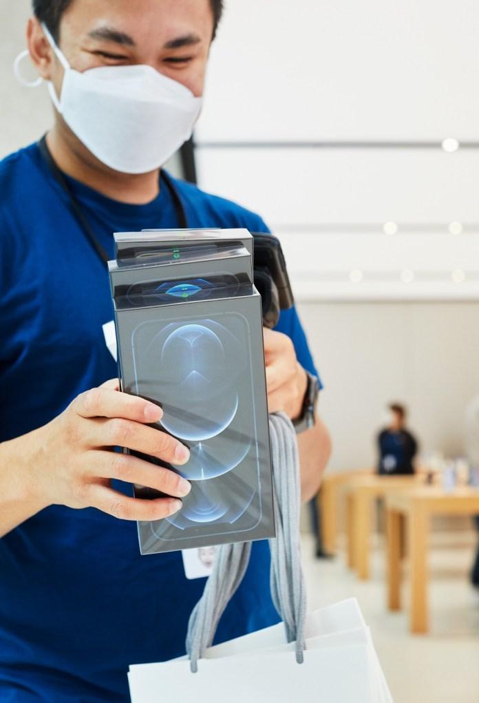 Un dipendente di Apple Sydney scansiona alcune confezioni di iPhone 12 Pro Max.