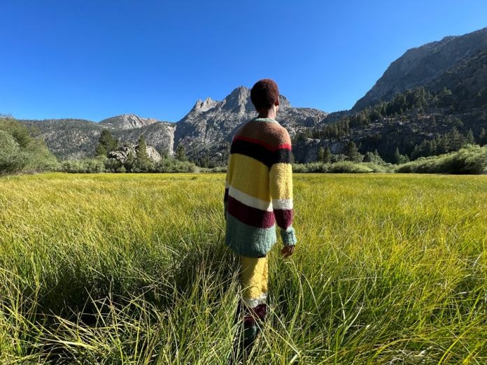 Man in colorful, lush landscape taken on iPhone 13 Pro's Wide camera.