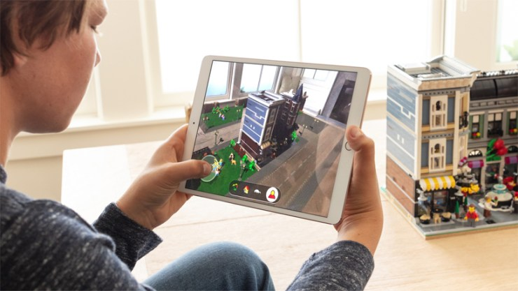 Boy sitting in front of a LEGO building in a room, holding an iPad with LEGO AR City on the screen.