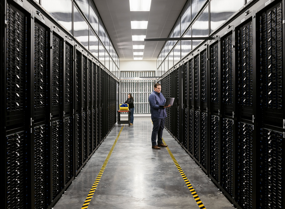 Two employees in a server room of an Apple data centre.