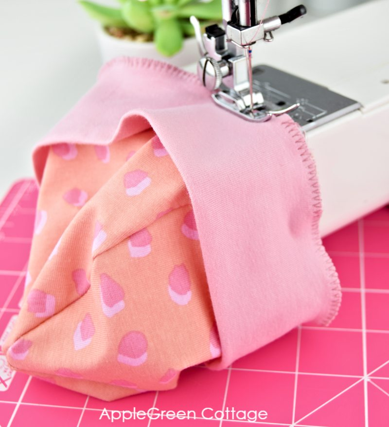 sewing machine with a semi-finished pink baby hat