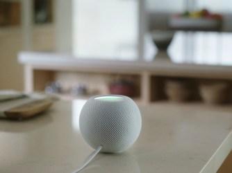 HomePod mini postavený na konferenčním stolku v obývacím pokoji