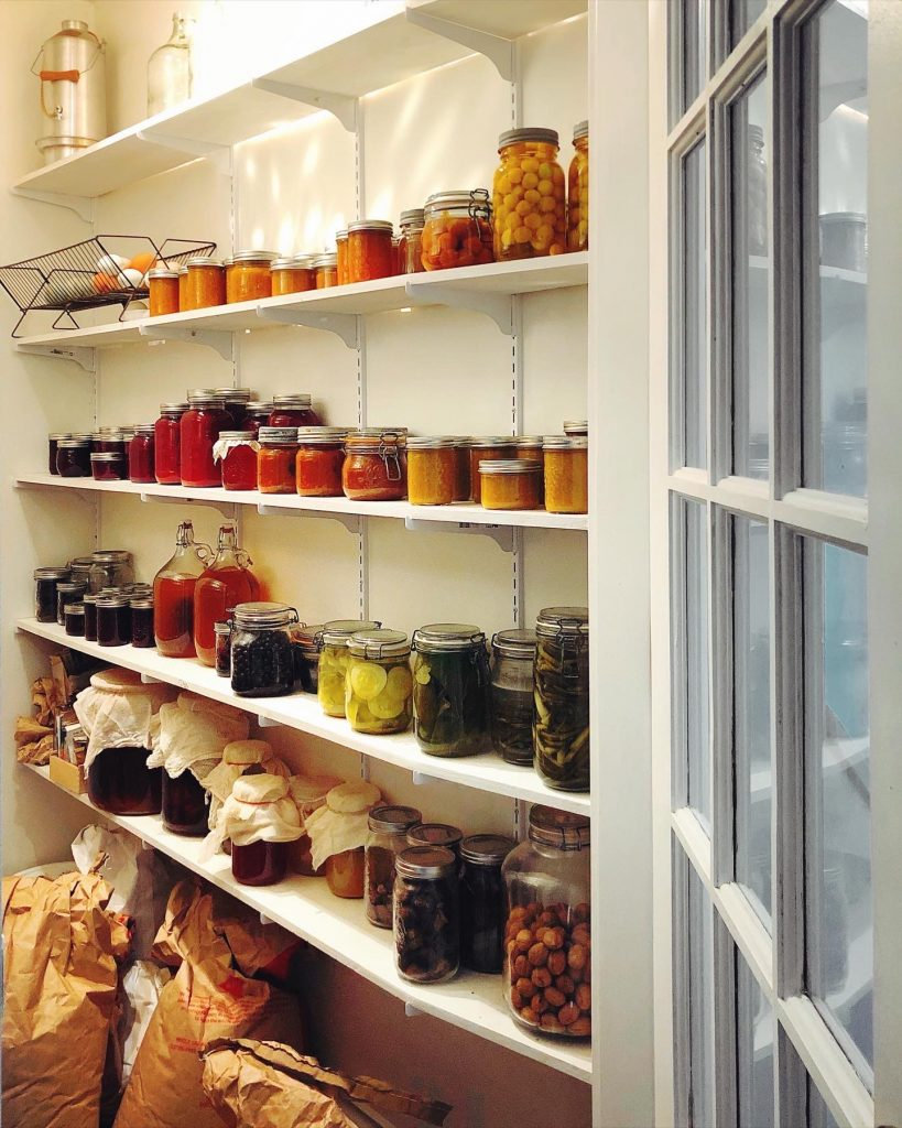 looking through the open pantry door at the shelves of preserves, dried fruit and nuts and sacks of grains.