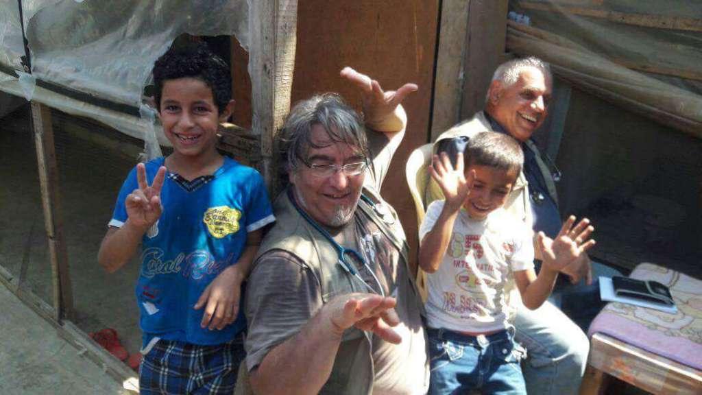 médico español y unos niños en un campo de refugiados