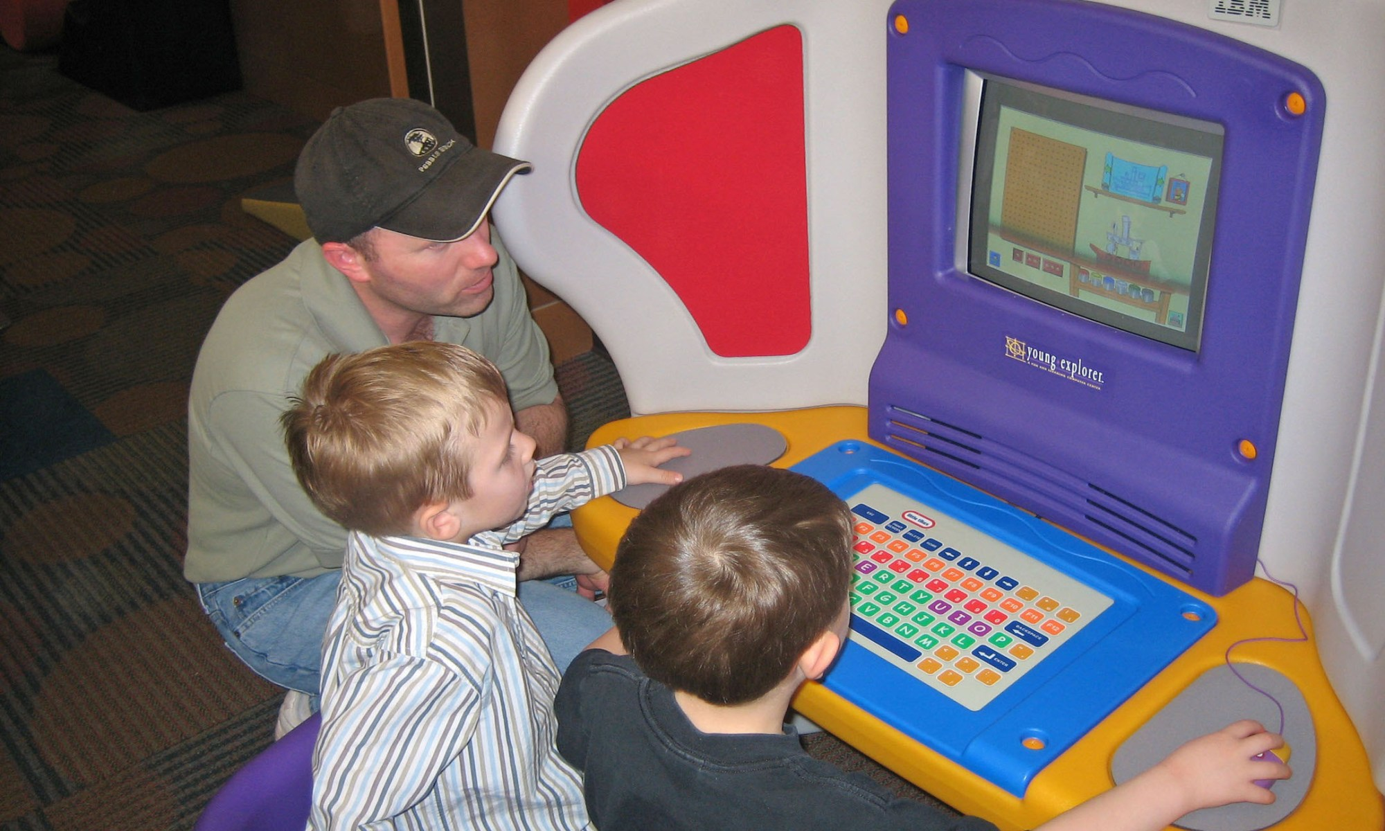 Father and sons at children's computer