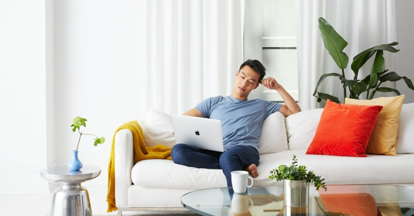 Man sitting on couch using laptop to sell furniture on AptDeco