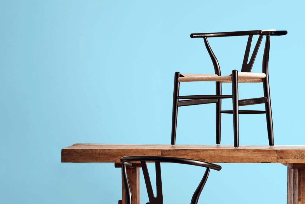 Wishbone chair on top of wooden table with light blue background