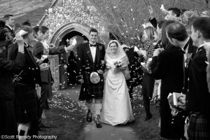 The bride and groom are covered in confetti by guests as they leave the church on their wedding day. The wedding was held at Apuldram Church, St Mary the Virgin Church, Apuldram, Chichester, West Sussex.