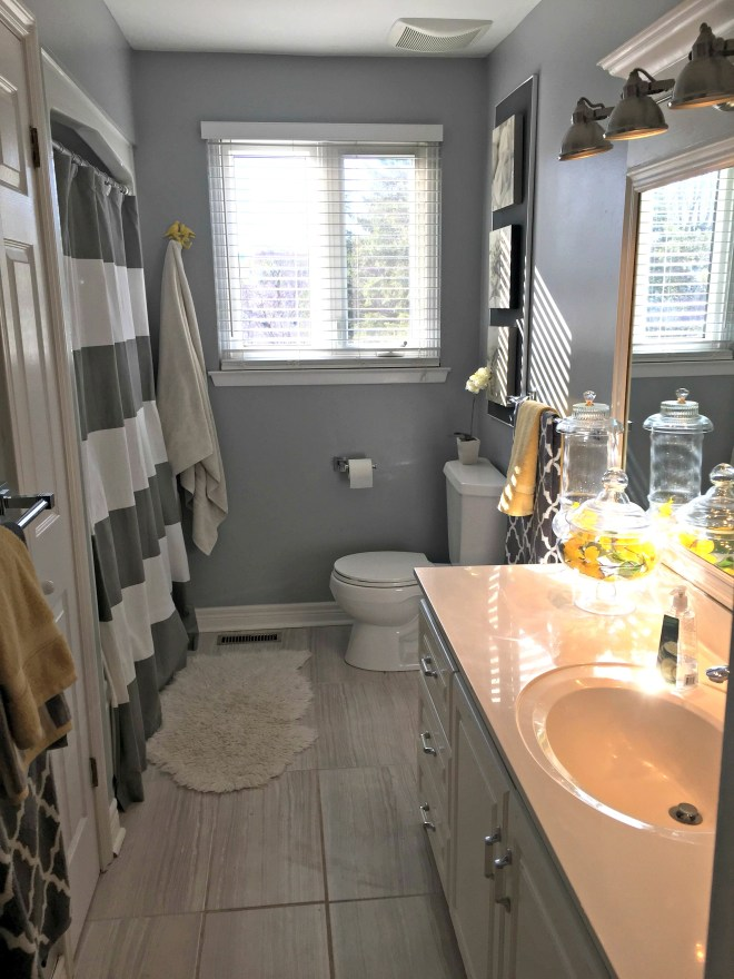 Kid's Bathroom Remodel. See how to transform an entire space using new flooring, paint and grey and yellow decor.