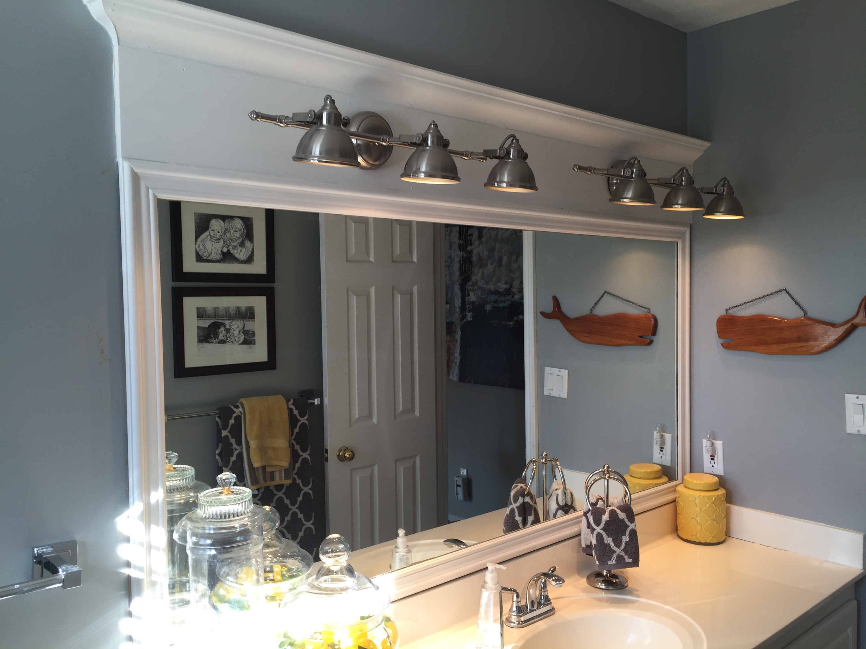 Kid's Bathroom Remodel. Frame around a builder's grade mirror. See how to transform an entire space using new flooring, paint and grey and yellow decor.