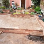 Reclaimed brick patio compliments brick and stainless steel water feature in garden
