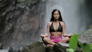 stock-footage-woman-doing-sitting-meditation-at-waterfall-in-the-tropics