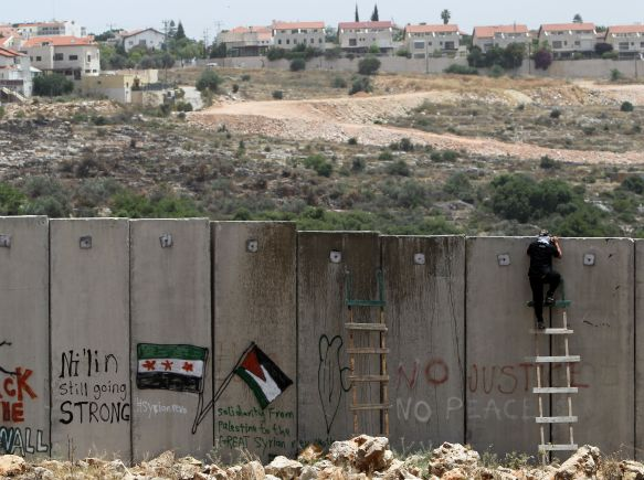 A Palestinian protester climbs Israel's controversial separation barrier during clashes with Israeli security forces following a demonstration against Israeli settlements and its separation wall, in the West Bank village of Nilin near the Jewish settlement of Hashmonaim (background), on May 31, 2013. AFP PHOTO/ ABBAS MOMANI (Photo credit should read ABBAS MOMANI/AFP/Getty Images)