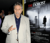 William Peter Blatty stands in front of a film poster for The Exorcist. Image Credit: The Huffington Post