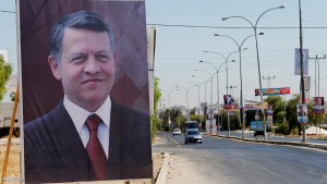 A poster of Jordan's King Abdullah is seen near electoral posters for parliamentary candidates ahead of the general elections on Tuesday, in Madaba city, near Amman