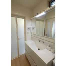 間口1.2mと広々とした洗面台をセレクト。 ミラーも広く、化粧品などの収納もばっちりです。 また、ドア横の壁面を一部へこませ、リモコンやスイッチを設置。キャビネット開閉時の干渉を避けました。