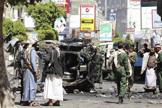 Armed Houthis gather around the wreckage of a vehicle set a blaze by angry protesters after Houthis fired on them in Yemen's central town of Ibb