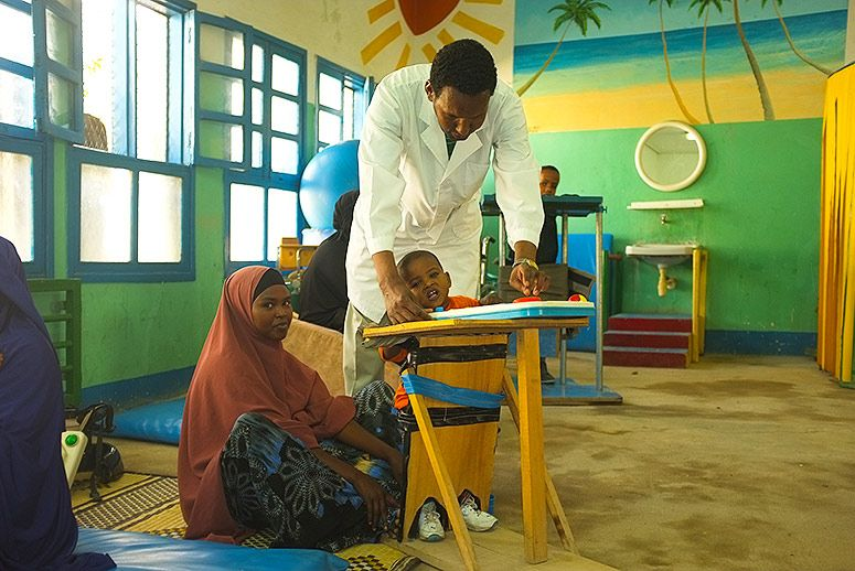 Abdillahi Mohammed, a doctor who has worked at DAN for 10 years, plays with one-year-old Abdifatah. Abdifatah's mother, 23-year-old Nimoali Ibrahim, traveled to Hargeisa from Berbera, a port city about two hours away, so her three children and young son could get therapy at DAN. (Photo: Amanda Sperber)