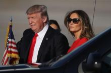 US President Donald Trump walks with his wife Melania Trump on the tarmac after he arrived on Air Force One at the Palm Beach International Airport for a visit to his Mar-a-Lago Resort for the weekend on February 3, 2017. (Photo by AFP)