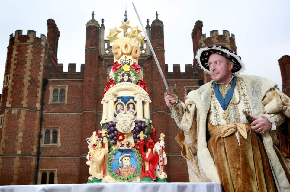 EDITORIAL USE ONLY King Henry VIII, played by Chris Bailey, celebrates Hampton Court PalaceÕs 500th birthday at the Tudor palace in East Molesey, Surrey, with an intricately detailed five tier cake, commissioned by Historic Royal Palaces from Choccywoccydoodah. PRESS ASSOCIATION Photo. Picture date: Tuesday February 10, 2015. Each of the cakeÕs tiers showcases a different century in the palaceÕs 500-year history rendered in chocolate. Henry VIIIÕs crown Ð which is on display at the palace, the Great Vine, architectural features and even the palaceÕs period of grace and favour occupancy have been translated into an edible artwork. The medallion of the top tier of the cake pays homage to the palaceÕs central role as a location for the London 2012 Olympic Games, where cyclist Bradley Wiggins won gold for Team GB. Photo credit should: Matt Alexander/PA Wire