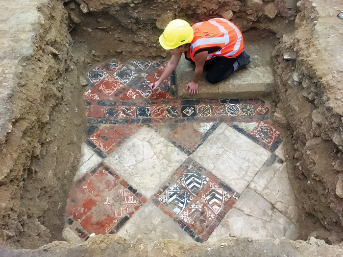 An archaeologist excavating the tiled floor of the abbey
