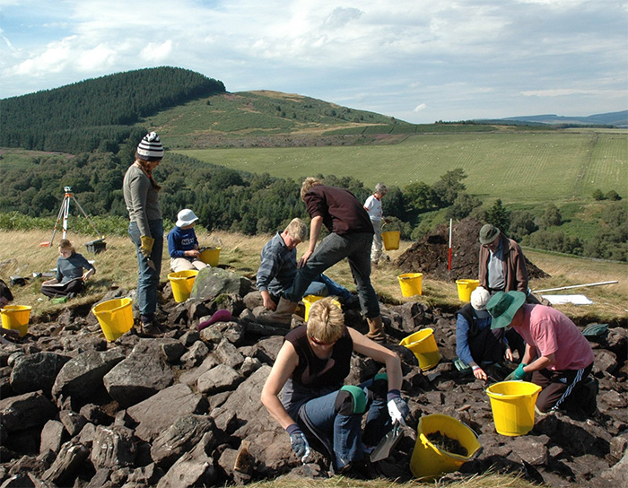 Excavations in forefront, hills of Northumberland behind them