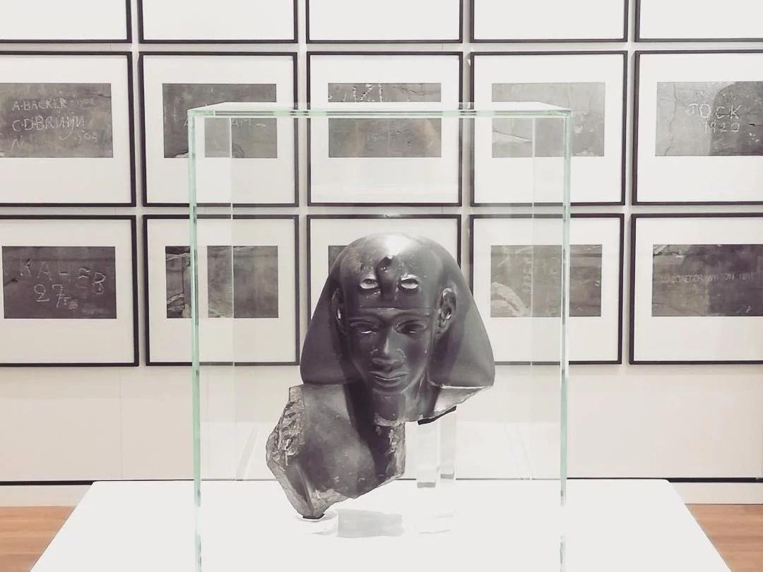Busto di statua composto da frammenti di una statua egiziana antica e da un volto realizzato nel Novecento. Alle spalle Signatures di S. Wachsmuth