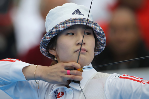 In this photo, Olympic champion Ki Bo Bae of Korea demonstrates a solid anchor point that's used by intermediate and advanced archers: drawing the bowstring to under her chin. Many beginning archers anchor by drawing the bowstring to the corner of their mouth.