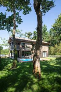maison bois familial avec piscine au millieu de la nature
