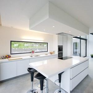 cuisine ouverte blanche dans maison bois moderne avec piscine
