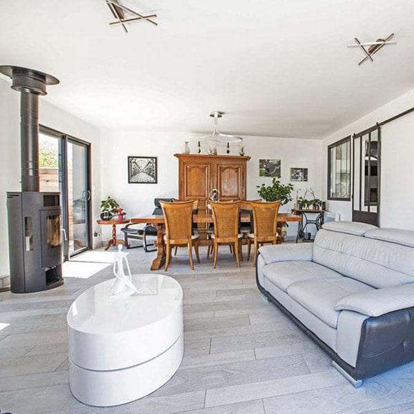 séjour avec cheminée et table à manger et armoire bois dans maison bois