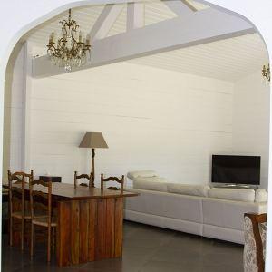 salon classique avec canapé et table à manger dans une maison jaune en kit