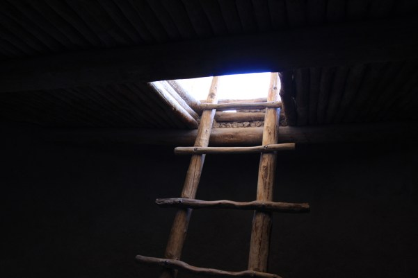 Ladder rising from darkness into a brightly lit opening