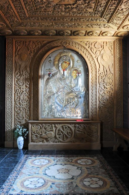 Икона Божьей матери , обрамленная уникальной резьбой по дереву.