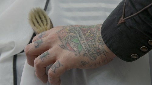 A barber's comforting hand resting on his client
