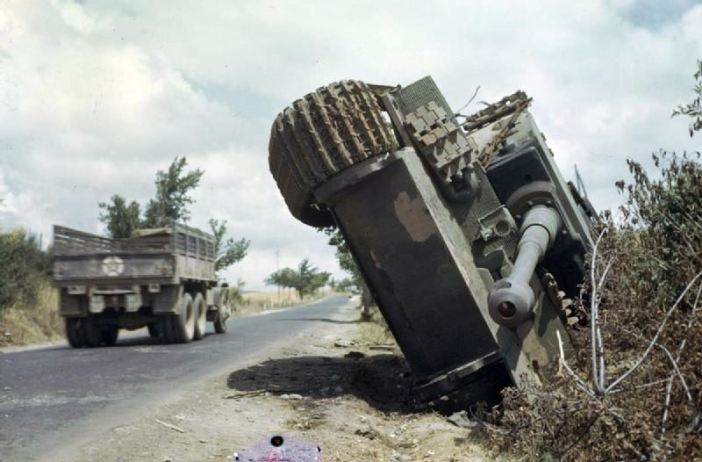 A German Tiger I tank on its side in a ditch, north of Rome, and an American lorry in the background driving past.