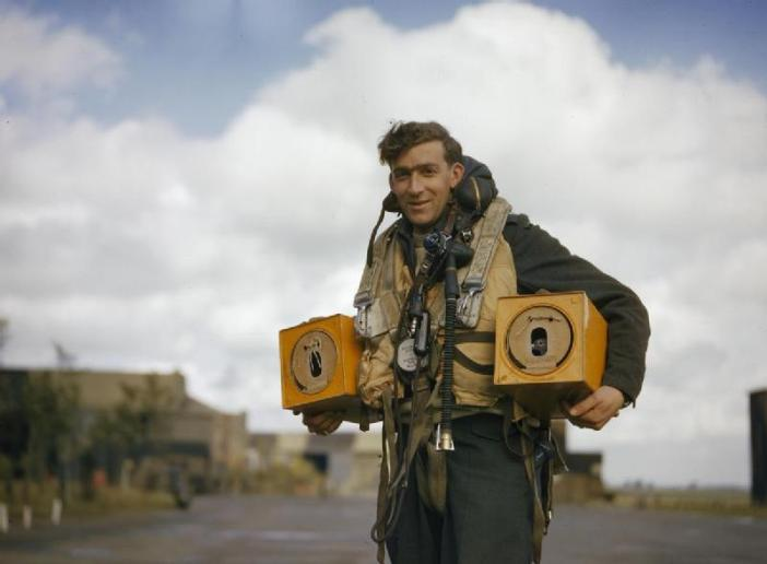 Canadian PO (A) S Jess, wireless operator of an Avro Lancaster bomber operating from Waddington, Lincolnshire carrying two pigeon boxes. Homing pigeons served as a means of communications in the event of a crash, ditching or radio failure.