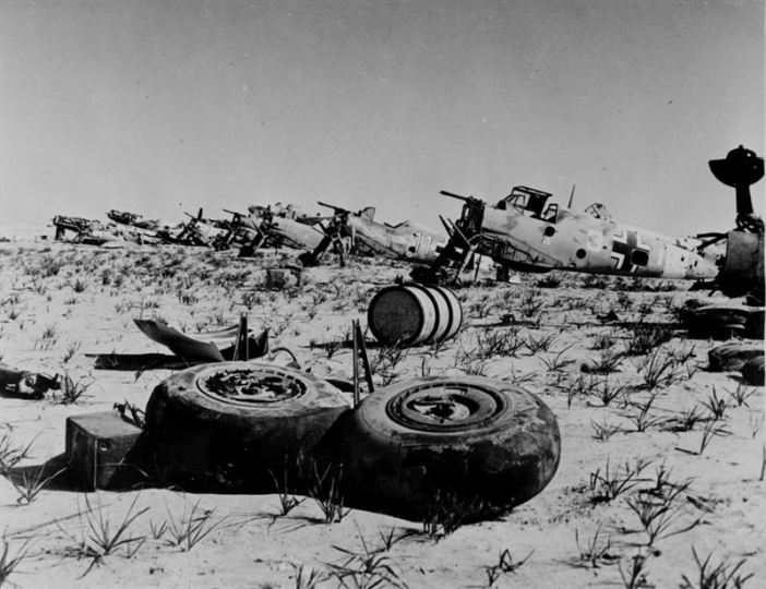 Wrecks of about eight German Messerschmitt Bf 109 fighters in North Africa (Tobruk?), circa 1942. The first fuselage wears the markings of III. Gruppe (3rd Group) of a fighter wing, probably III./JG 27. An abandoned Messerschmitt Bf 110 also seems to be visible in the center background.