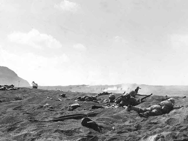 Original Description: A reserve of Fourth Division Marines, burrowed into the black sand of Iwo Jima, awaits its turn to move up on D-Day, February 19. Almost lost in the smoke haze over the battlefield, the attack line ahead is charging forward.