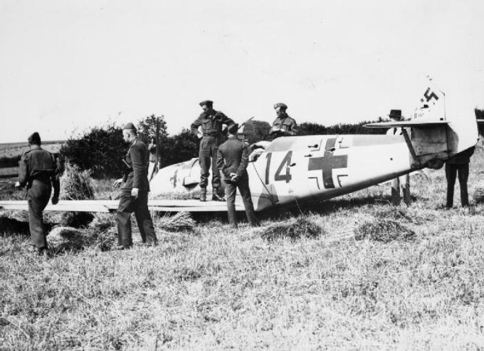 "Army officers inspect the wreckage of Messerschmitt Bf 109E-1 (W.Nr. 3367) ""Red 14"" of 2./JG52, which crash-landed in a wheatfield at Mays Farm, Selmeston, near Lewes in Sussex, 12 August 1940. Its pilot, Unteroffizier Leo Zaunbrecher, was captured."