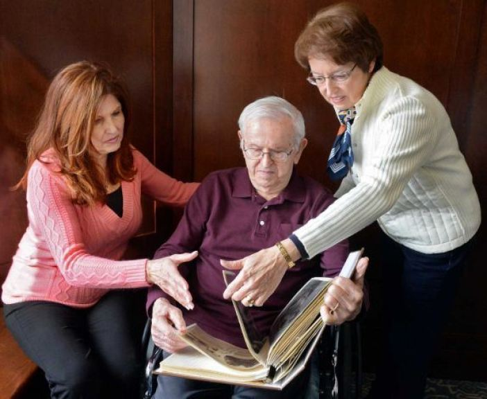 WWII Staff Sgt. Joseph W. Jamro, 93, center, who was shot down as a tail gunner on a Liberator bomber over Romania in 1944 looks through a scrap book with daughters Peggy Warzala, left, and Barbara Brandone at the Capital Living Nursing and Rehabilitation Centre Thursday Feb. 26, 2015 in Schenectady, NY. His family is working to get him a Silver Star. (John Carl D'Annibale / Times Union)