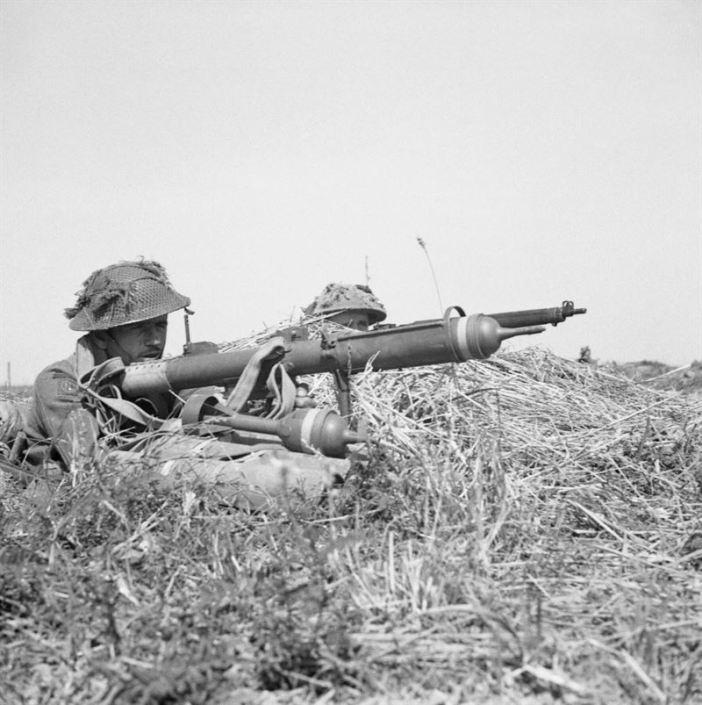 A British infantryman prepares to fire a PIAT anti-tank weapon, Normandy, 9 August 1944.