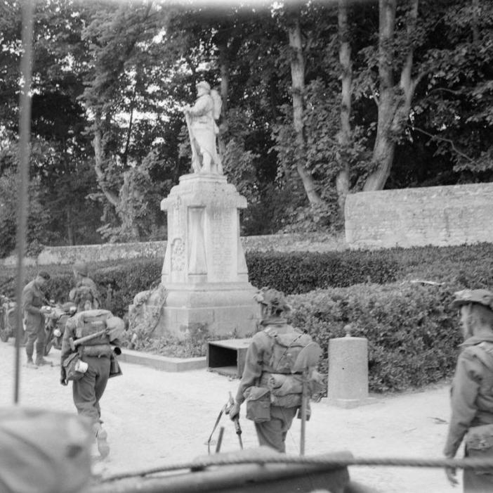 British 3rd Division troops passing a First World War memorial in Hermanville-sur-Mer, 6 June 1944.