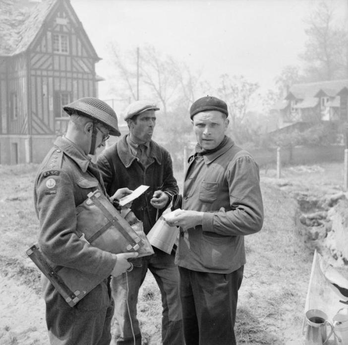 French civilians show their identity cards to a British Royal Army Service Corps captain of No. 6 Beach Group in La Brèche d'Hermanville, 6 June 1944.