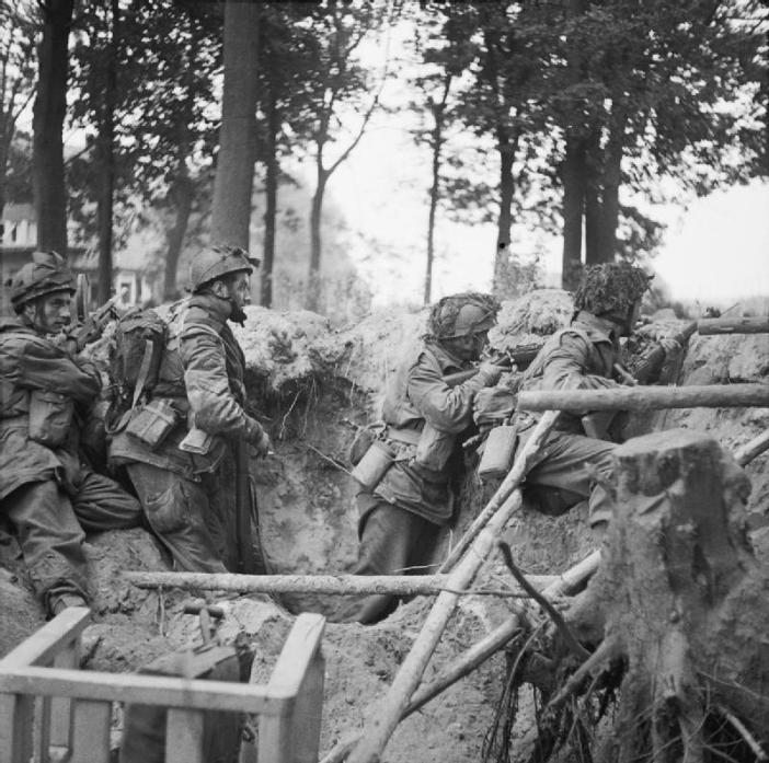 Four men of the 1st Paratroop Battalion, 1st (British) Airborne Division, take cover in a shell hole outside Arnhem. 17 September 1944.