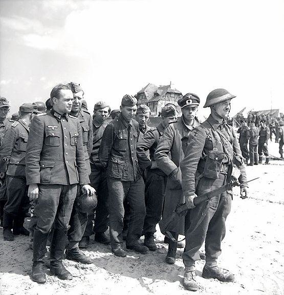 Two German officers in a group of prisoners who surrendered to Canadian troops in Courseulles-sur-Mer - June 6, 1944. (Credits: Library and Archives Canada)