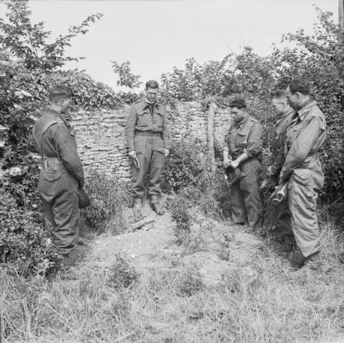 Reverend Victor Leach, Padre of 13/18 Hussars, reading the burial service for a fallen tankman who was killed in action with the German 21st Panzer Division in the Hermanville sur Mer sector of Normandy, France. The dead man's comrades stand in silent tribute at the graveside.